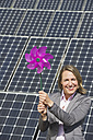 Germany, Munich, Woman holding paper windmill against solar panels, smiling, portrait - WESTF017831