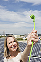 Germany, Munich, Woman holding electric cord in solar energy, smiling - WESTF017834