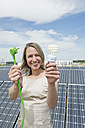 Germany, Munich, Woman holding electric cord and lightbulb in solar energy, smiling, portrait - WESTF017837