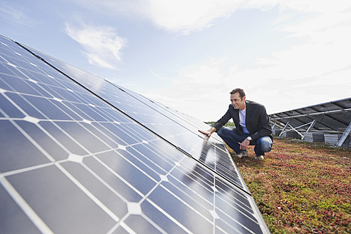 Germany, Munich, Man touching solar panel in solar plant - WESTF017849