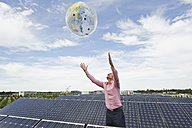 Germany, Munich, Mature man with globe in solar plant - WESTF017864