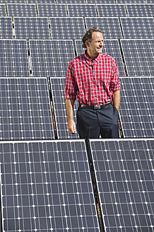 Germany, Munich, Mature man standing in solar plant, smiling - WESTF017867