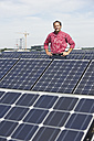 Germany, Munich, Mature man standing in solar plant, smiling, portrait - WESTF017870