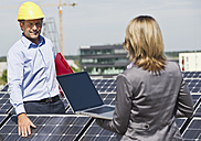 Germany, Munich, Engineers with laptop and discussing in solar plant - WESTF017888