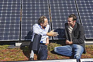 Germany, Munich, Two man sitting and talking in solar plant - WESTF017897