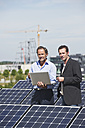 Germany, Munich, Engineer and man discussing in solar plant - WESTF017900