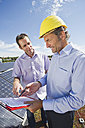 Germany, Munich, Man discussing with engineer in solar plant - WESTF017903