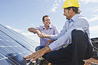 Germany, Munich, Man shaking hands with engineer in solar plant, smiling - WESTF017906