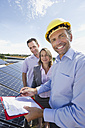 Germany, Munich, Engineer with man and woman in solar plant, smiling, portrait - WESTF017909