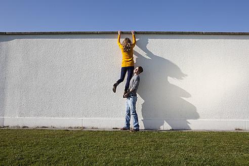 Germany, Bavaria, Munich, Young couple climbing wall - RBF000729