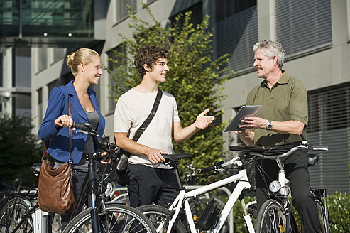 Germany, Bavaria, People with cycle discussing together, smiling - RNF000724