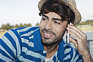 Germany, Cologne, Young man using cell phone, smiling - WESTF017975