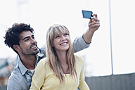 Germany, Cologne, Young couple using cell phone for capturing photo, smiling - WESTF018011