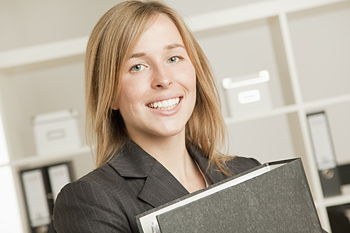 Young woman with folder in office, smiling, portrait - RIMF000049
