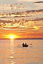 Germany, Baden-Wurttemberg, Langenargen, People in boat at sunset - WDF001079