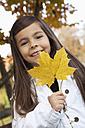 Germany, Huglfing, Girl holding leaf, smiling, portrait - RIMF000068