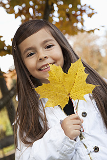 Germany, Huglfing, Girl holding leaf, smiling, portrait - RIMF000068