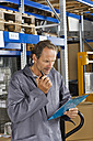 Germany, Bavaria, Munich, Manual worker checking list in warehouse - WESTF018057