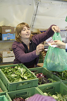 Germany, Upper Bavaria, Wolfratshausen, Woman buying vegetables from market - TCF002125