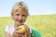 Germany, Bavaria, Girl with apple in grass, smiling, portrait - RNF000763