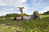 Germany, Bavaria, Boy playing with model airplane in park, smiling, portrait - SKF000547