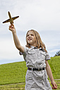Germany, Bavaria, Girl playing with model airplane in park - SKF000559