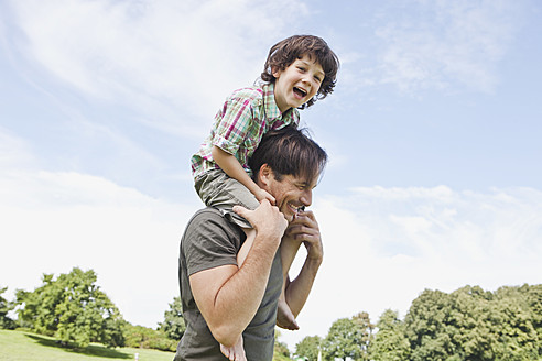 Germany, Bavaria, Father carrying son on shoulder in park, smiling - SKF000568