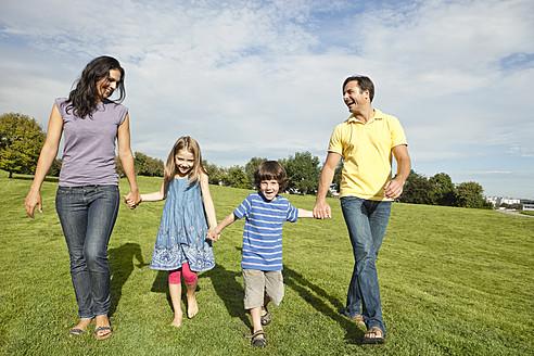 Germany, Bavaria, Family walking in grass at park - SKF000622