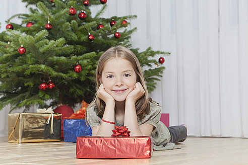 Germany, Munich, Girl with present near christmas tree - SKF000631
