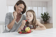 Germany, Munich, Mother and daughter eating fruits, smiling - SKF000655