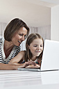 Germany, Munich, Mother and daughter using laptop, smiling - SKF000658