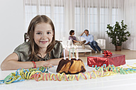 Germany, Munich, Girl with birthday cake, parents in background - SKF000667