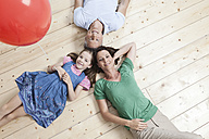 Germany, Munich, Family lying on floor, smiling, portrait - SKF000685