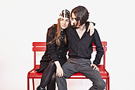 Mid adult couple sitting on bench against white background - NDF000185