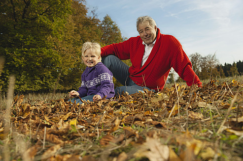Germany, Bavaria, Grandfather and granddaughter sitting grass, smiling - RNF000791