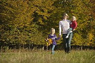 Germany, Bavaria, Mother and daughters walking in meadow - RNF000821