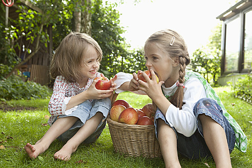 Germany, Bavaria, Munich, Girls eating apple in garden - RBF000787