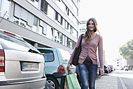 Germany, Cologne, Young woman with shopping bags, smiling, portrait - FMKF000360