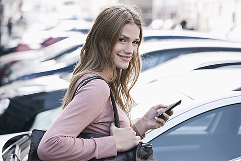 Germany, Cologne, Young woman with phone near parking lot, smiling, portrait - FMKF000363