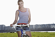 Germany, Cologne, Young woman with bicycle, smiling, portrait - FMKF000375