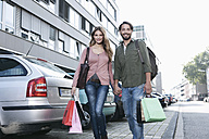 Germany, Cologne, Young couple with shopping bags near parking lot, smiling - FMKF000390