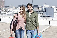 Germany, Cologne, Young couple with shopping bags, smiling, portrait - FMKF000393