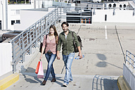 Germany, Cologne, Young couple with shopping bags, smiling, portrait - FMKF000396