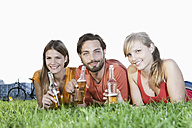 Germany, Cologne, Young man and woman lying in grass with beer bottles, smiling, portrait - FMKF000417
