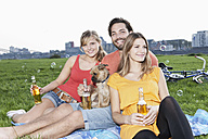 Germany, Cologne, Young man and woman with dog and beer bottle in grass, smiling - FMKF000435