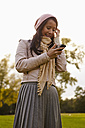 Germany, Cologne, Young woman with cell phone in park, smiling - RHF000006