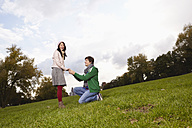 Germany, Cologne, Young man proposing woman in park, smiling - RHF000021