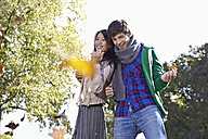 Germany, Cologne, Young couple in park, smiling - RHF000024