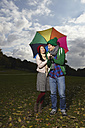 Germany, Cologne, Young couple with umbrella in park, smiling - RHF000030