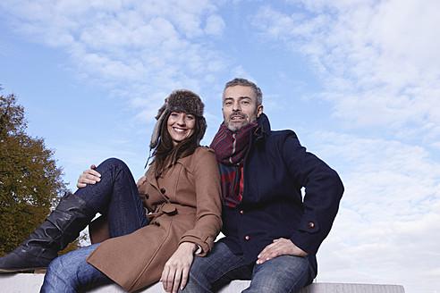 Germany, Cologne, Couple sitting on bridge, smiling, portrait - RHF000042